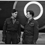 """Group Photo– Their mates of the RCAF Bomber Group squadron commanded by W/C J. D. """"Pat"""" Patterson, DFC have given up trying to tell the Byers twins apart. The two lads, pictured above, joined the RCAF together as engine fitters, re mustered together, did all their training together and were posted to the same squadron overseas. Within 24- hours of arrival they were on their way to Hanover taking part in one of the heaviest raids yet staged by the Canadian Group, Sgt. Bill Byers is shown at LEFT, and his brother George at RIGHT. Bill doesn't believe in luck charts, but George wears a white ivory skull on his battle dress. Their home is at 913 West Fifth Ave., West Vancouver, BC."""